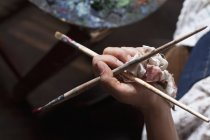 Crop female hand holding paintbrushes against table — Stock Photo