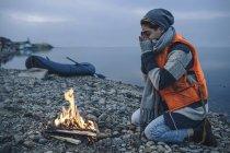 Adolescente che si siede al falò sulla riva del lago nel cielo coperto — Foto stock