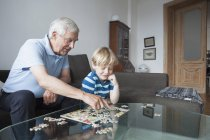 Grandfather solving jigsaw puzzle with grandson in living room at home — Stock Photo