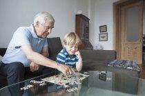 Résoudre le puzzle avec petit-fils dans la salle de séjour à la maison de grand-père — Photo de stock