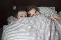 Porträt eines jungen schwulen Paares, das durch Laken im Bett blickt — Stockfoto