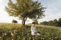Mulher meditando no campo gramado — Fotografia de Stock