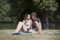 Молода пара, сидячи на пікніку ковдру, тримаючи кавун фрагмента — стокове фото