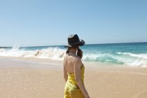 Rear view of woman in hat walking on beach and looking at waves — Stock Photo