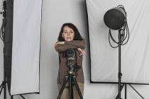 Retrato del fotógrafo mujer madura seguro apoyado sobre trípode de cámara en estudio fotográfico - foto de stock