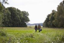 Paar trägt Campingzubehör bei Spaziergang durch Feld — Stockfoto