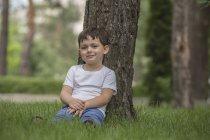 Портрет милого мальчика, расслабляющегося на фоне дерева в парке — стоковое фото