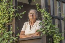 Задумчивая пожилая женщина смотрит в сторону, стоя на балконе — стоковое фото