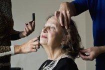 Truccatore applicando polvere compatta sul viso della donna — Foto stock
