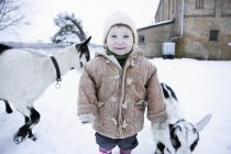 Baby girl standing with goats on background in winter and looking at camera — Stock Photo