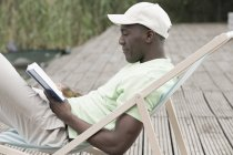 Man reading and relaxing on deck chair — Stock Photo