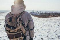 Vue arrière du randonneur debout sur un paysage enneigé — Photo de stock