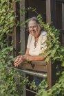 Портрет пожилой женщины с зажатыми руками, стоящей на балконе — стоковое фото