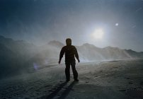 Silhouette of person standing on snowy mountain slope — Stock Photo
