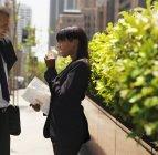 Бизнесвумен держит цветок и разговаривает с бизнесменом на открытом воздухе — стоковое фото