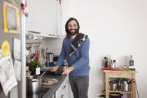 Smiling man looking away while preparing food in domestic kitchen — Stockfoto
