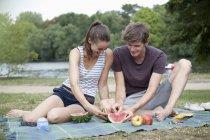 Молода пара, маючи пікнік, різання кавун — стокове фото
