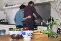 Vegetables on kitchen table over couple cooking in background — Stock Photo