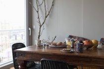 Café da manhã na mesa de jantar de madeira na janela — Fotografia de Stock