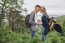 Couple amoureux tenant la main tout en se tenant au milieu des plantes dans la forêt — Photo de stock