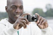 Крупный план человека с помощью цифровой камеры — стоковое фото