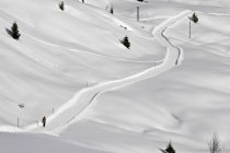 Distant view of person walking up hill through snow laden footpath — Stock Photo