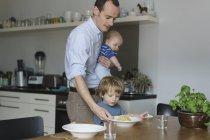 Батько балансова малюк даючи їжу до сина в обідній стіл — стокове фото