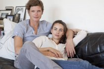 Portrait of Young couple sitting on sofa — Stock Photo