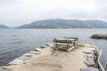 Tavolo da picnic vuoto sul molo sul lago di montagna — Foto stock