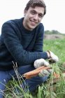 Portrait of smiling young man harvesting carrots in field — Stock Photo