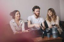Возбужденных молодых друзей, играть в видео игры на дому — стоковое фото