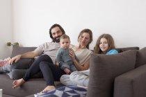 Retrato de la familia con dos niños sentados en el sofá en la sala de estar - foto de stock