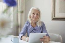 Portrait de femme senior confiante, tenant la tablette numérique à tablette — Photo de stock