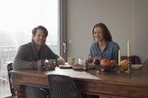 Retrato de casal tomando café da manhã na mesa de jantar a sorrir — Fotografia de Stock