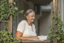 Senior woman holding book while looking away on balcony — Stock Photo