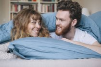 Loving young couple looking at each other while lying in bed — Stock Photo