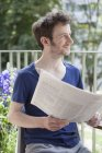 Man looking away while holding newspaper at porch — Stock Photo