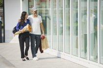 Couple marchant sur le trottoir en face de la paroi de verre dans la ville de jour ensoleillé — Photo de stock