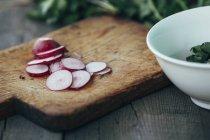 Close-up vista das fatias de rabanete na placa de corte pela taça na mesa — Fotografia de Stock