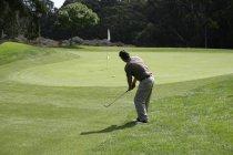 Вид сзади на гольфиста после удара мячом — стоковое фото