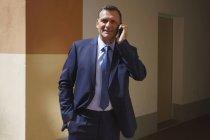 Уверенный бизнесмен разговаривает по мобильному телефону, стоя в офисе — стоковое фото