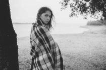 Retrato de adolescente envolvido no pé de cobertor na costa do lago — Fotografia de Stock