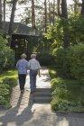 Coppia anziana camminando verso casa tra le piante — Foto stock