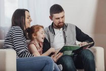 Parents reading book with daughter while sitting on sofa at home — Stock Photo