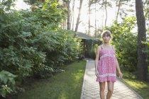 Woman wearing pink dress walking on pathway amidst plants in yard — Stock Photo