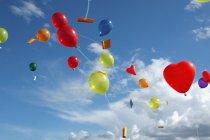 Цветные гелиевых шаров с сообщениями, плавающие в небе выше — стоковое фото