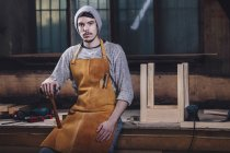 Portrait of carpenter holding hammer while sitting on bench at workshop — Stock Photo