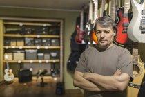 Портрет уверенного владельца мужского пола, стоящего с руками, скрещенными в магазине гитарами — стоковое фото