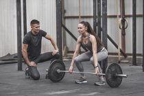 Male instructor looking at female athlete lifting barbell during crossfit training — Stock Photo