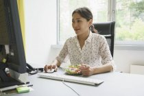 Businesswoman using computer while having salad in creative office — Stock Photo